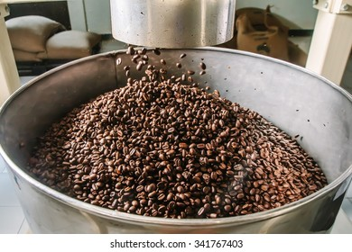 The freshly roasted coffee beans from a coffee roaster being poured into the tank.