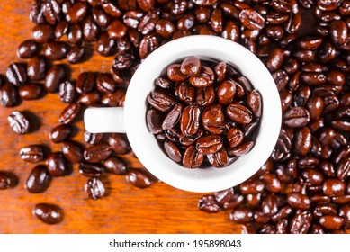freshly roasted shiny coffee beans in a cup on rustic wooden background