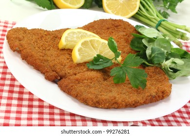 freshly roasted wiener schnitzel with lemon slices and parsley