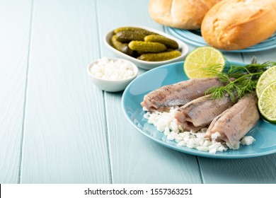 Freshly salted herring fish, traditional dutch delicacy called hollandse nieuwe on turquoise plate and wooden background. European food concept with copy space.