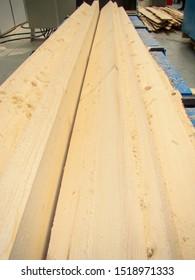 Freshly sawn boards on the sawing line of logs. Sawdust shavings.