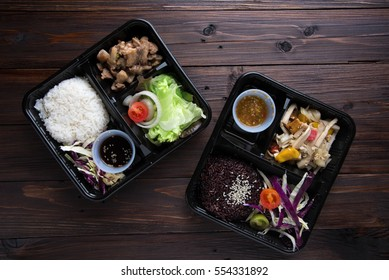 Freshly served bento box on wooden table background. top view
