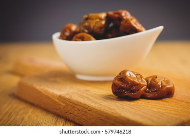 Freshly served pickled plums on a wooden plate