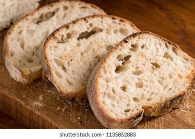 Freshly sliced sliced panini bread on a wooden cutting board in soft window light