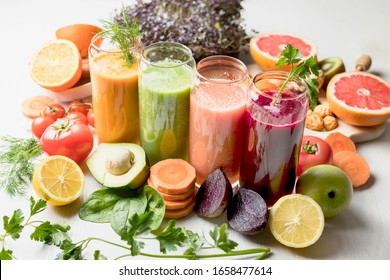 freshly squeezed juice, fruit and vegetable smoothies in glass glasses on a white table decorated with a composition of fruit