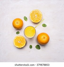 freshly squeezed juice from oranges in a glass with a straw, spread out around the oranges and mint on wooden rustic background top view close up