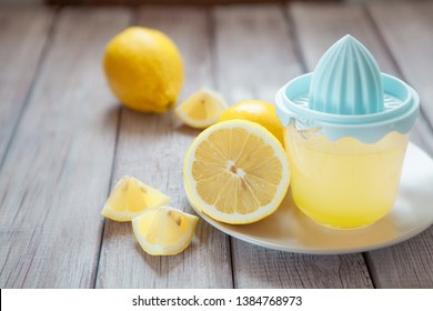 Freshly squeezed lemon juice in juicer on wooden table, copy space
