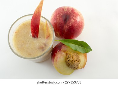 Freshly squeezed natural peach juice and fresh peaches on white