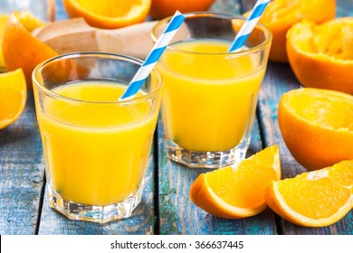 freshly squeezed orange juice in a glass with straws with slice of fruits