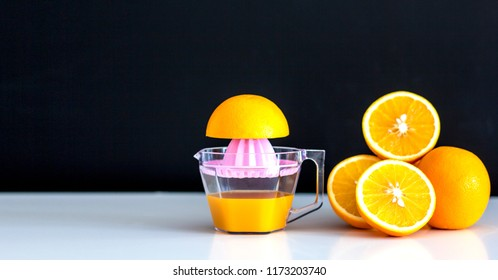 Freshly squeezed orange juice and orange on dark background. Health cocept.