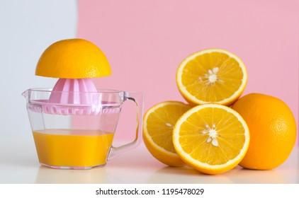 Freshly squeezed orange juice and orange on pink background. Health cocept.