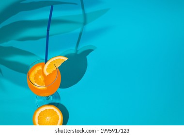 Freshly squeezed orange. Stil life. Shade of palm leaves. Blue background - Shutterstock ID 1995917123