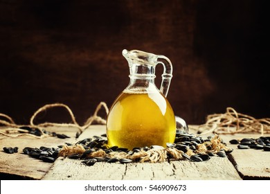 Freshly squeezed sunflower oil in a glass jug, vintage wooden background, rustic style, selective focus