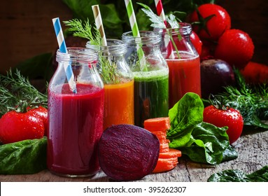 Freshly squeezed vegetable juice in bottles, useful vitamin cocktail, old wooden background, selective focus
