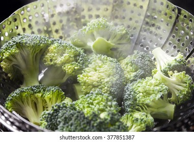 Freshly steamed green broccoli in skimmer pot with steam