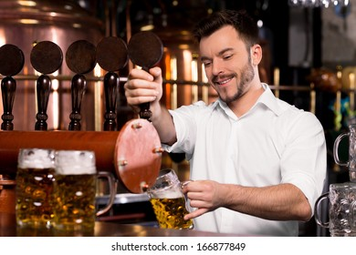 Freshly tapped beer. Cheerful young bartender pouring beer and smiling