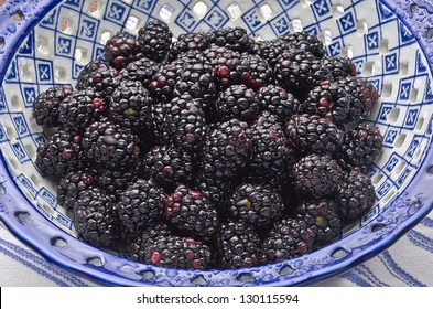 Freshly washed blackberries in decorative blue bowl