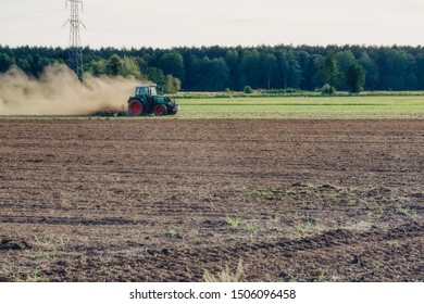 freshly worked field with a cultivator, a large cloud of dust, dry land due to lack of rainfall, plowing and work and tillage of sowing winter crops