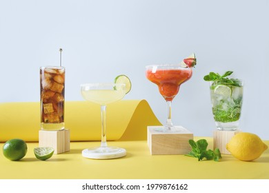 Freshness different cocktails mojito, cuba libre, margarita cocktail with lime, strawberries, and lemon on modern yellow background. Summer freshness beverage for festive party. Holiday aperitif.
