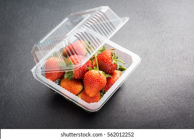 freshness strawberry in transparent plastic package on black colored wood plank
