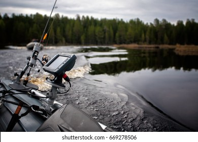 Freshwater fishing equipment on Inflatable boat riding the lake on overcast day
