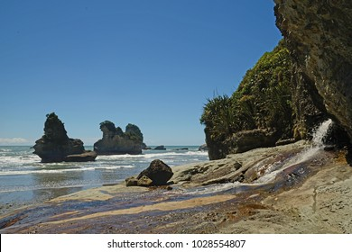 A freshwater stream empties on to a West Coast beach, South Island, New Zealand