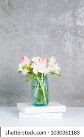 fressia and tulip flowers in a blue glass jar