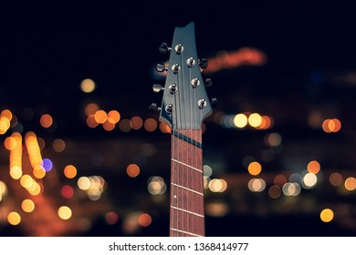 Fret Electric Guitar nighttime photo with a blurred background, multicolored bokeh in the background.