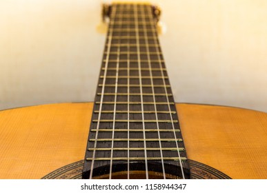 Fretboard and neck of a classical or spanish guitar with blur effect in background and clear natural light. Close up view of a musical instrument.