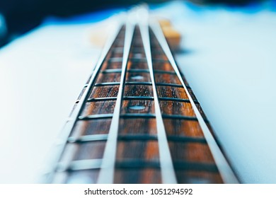 Frets on bass guitar. Close up. Vintage old retro bass in studio. Trendy cold style