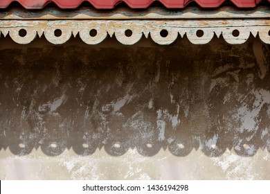Fretwork on the house eaves in front of concrete wall