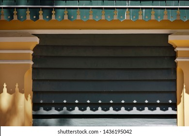 Fretwork on the house eaves in front of wooden wall