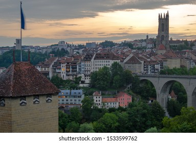 Fribourg, Switzerland cityscape at sunset with the the Red Tower, Saint-Nicholas Cathedral, and part of the Zähringen Bridge