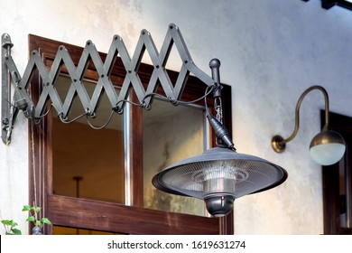 friction pantograph pendant electric heater mounted on the wall of the building facade with a brown window, black heater in the loft style close-up.