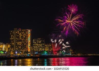 Friday night fireworks show in waikiki hawaii oahu - see lights reflecting in the pacific ocean water