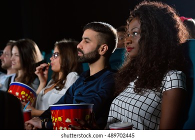 Friday nights. Group of multicultural friends enjoying a movie together at the cinema
