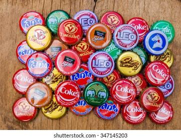 Friday,4 December 2015: in Chumphon Thailand ,Coca Cola,Sprite,Fanta, leo,oza,splash,chang Bottle Caps on wood table.