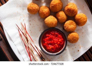 Fried Arancini rice balls . Typical Sicilian street food with spicy sauce