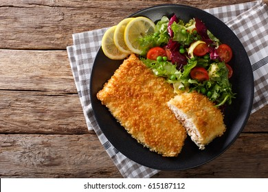 Fried Arctic char fish fillet in breadcrumbs and fresh vegetable salad close-up on a plate. horizontal view from above