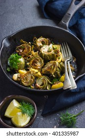 fried artichokes with garlic and lemon on pan, top view