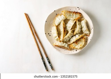 Fried asian dumplings Gyozas potstickers in white ceramic plate served with chopsticks and soy spring onion sauce over white marble background. Flat lay, space. Asian dinner