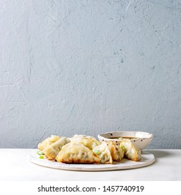 Fried asian dumplings Gyozas potstickers in white ceramic plate served with bowl of soy onion sauce over white marble table. Grey wall at background. Asian dinner. Square image
