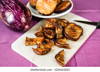 Fried aubergine sliced on kitchen board with knife, baked aubergine circles on small white plate and raw aubergine, all on violet background.