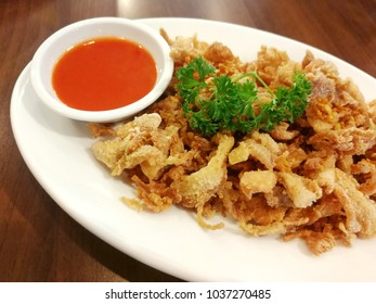 Fried Bacon with Vegetables and Chili Sauce In a white plate on a brown wooden table.