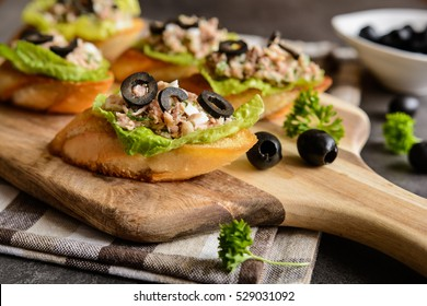 Fried baguette slices with tuna meat, olives, onion, egg and lettuce
