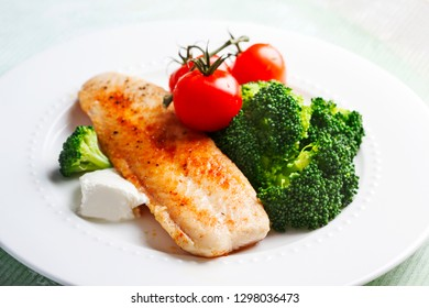 Fried Basa Fillet with sauce, broccoli and fresh tomato.