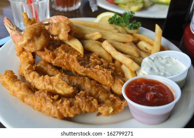 Fried battered seafood with french fries and dipping sauce