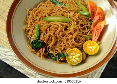Fried bee hoon with vegetables. Famous Chinese Food in South East Asia. Rice vermicelli stir fried with vegetables, tomato and lime.
