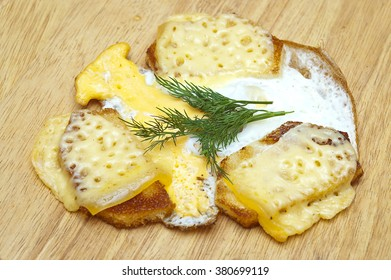 Fried bread on a wooden board with cheese and egg
