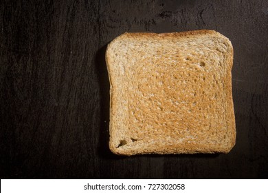 Fried bread toast on a black wooden surface